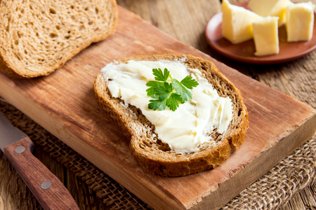 Butter and bread for breakfast, with parsley over rustic wooden background close up