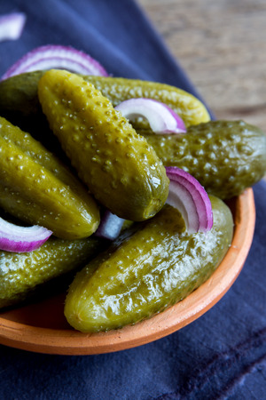 marinated gherkins: Pickles in ceramic bowl over rustic wooden background close up Stock Photo