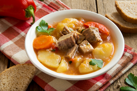 Tasty stew with meat and vegetables in bowl with ingredients over rustic wooden table