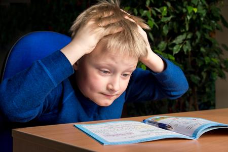 피곤 지루한 소년은 자신의 어려운 학교 숙제를하고 싶지 않아 스톡 콘텐츠