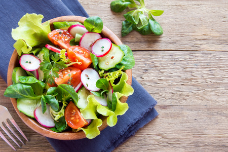 Fresh green spring vegetable salad with cucumber, radish, tomatoes and seeds in wooden bowl over rustic background with copy space