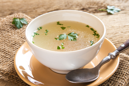 Chicken broth with parsley in white bowl close up Reklamní fotografie