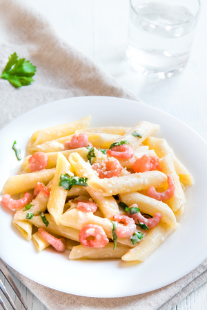 grated parmesan cheese: Penne pasta with shrimps, cream sauce and grated parmesan cheese Stock Photo
