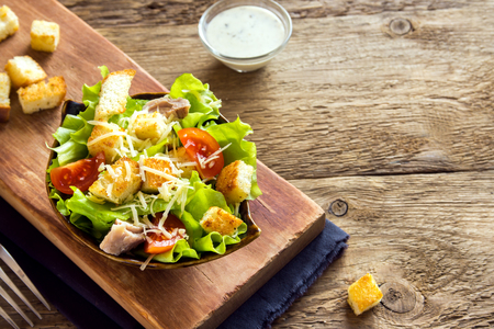 Chicken caesar salad with cheese, tomatoes and croutons over rustic wooden background