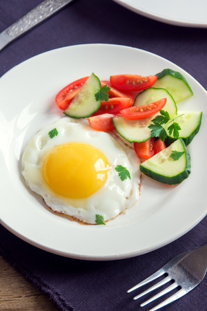 english cucumber: Fried egg with fresh vegetable salad on plate for breakfast Stock Photo