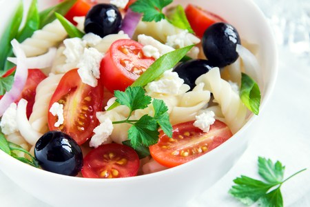 fussili: Pasta salad with vegetables, olives and feta over white background