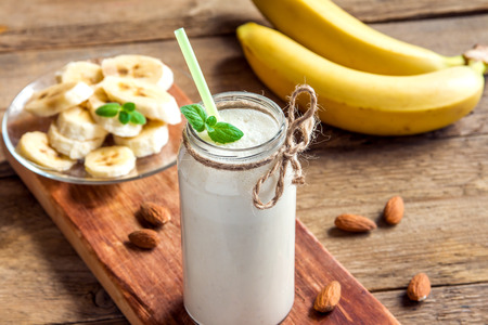Banana smoothie with mint and almond over rustic wooden background