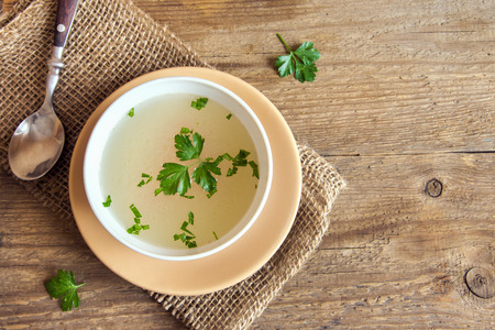 Chicken broth with parsley in white bowl over wooden background with copy space