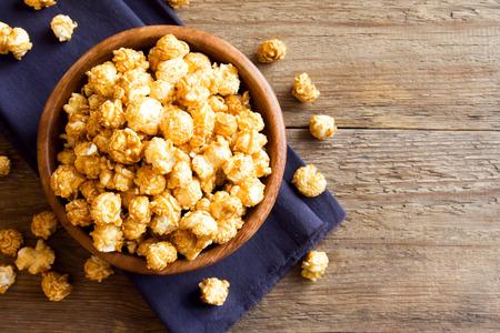 Homemade caramel popcorn in wooden bowl