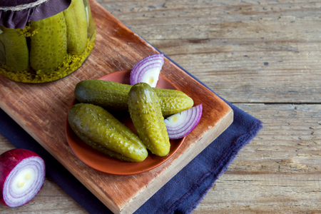 marinated gherkins: Homemade pickles with red onion over rustic wooden background with copy space