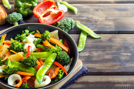 Healthy stir fried vegetables in the pan and ingredients over wooden background with copy space Foto de archivo