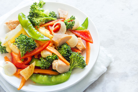 Healthy stir fried vegetables with chicken on white plate with copy space