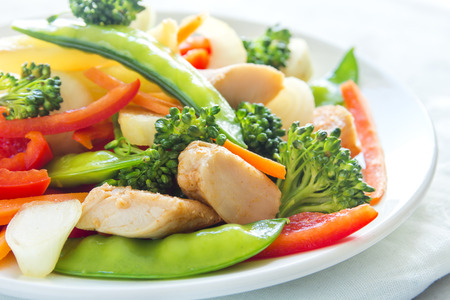 stir up: Healthy stir fried vegetables with chicken on white plate close up