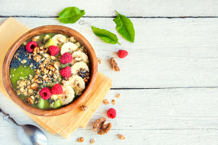 Healthy breakfast green smoothie bowl topped with fruits, nuts, berries and seeds over white wooden background with copy space