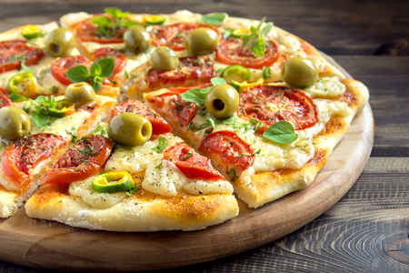 Homemade vegetable pizza with tomatoes, green olives, pepper, basil, oregano and cheese on wooden table with copy space Stock Photo