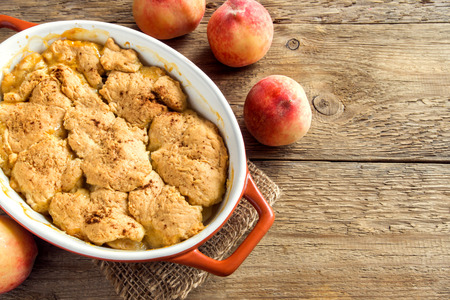 Homemade peach cobbler (crumble) in baking dish over rustic wooden background Stock Photo