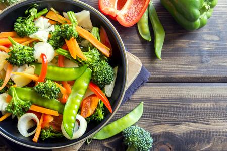 Healthy stir fried vegetables in the pan and ingredients close up, vegetarian food