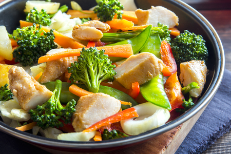 stir up: Healthy stir fried vegetables with chicken on pan close up Stock Photo
