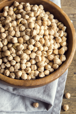 Raw organic chickpeas in rustic wooden bowl, healthy vegan food Stock Photo