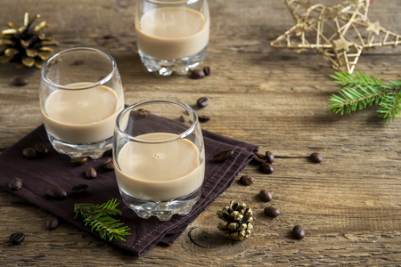 Irish cream coffee liqueur with Christmas decoration and ornaments over rustic wooden background - festive Christmas alcoholic drink 스톡 콘텐츠