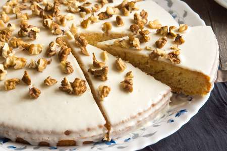 walnut cake: Homemade pumpkin and walnut cake with cream icing over rustic wooden table - healthy homemade pastry