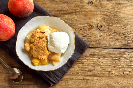 Homemade peach cobbler with vanilla ice cream over rustic wooden background with copy space - healthy pastry dessert