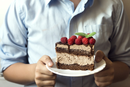 Closeup hands holding piece of delicious chocolate cake with raspberries and mint in white plate