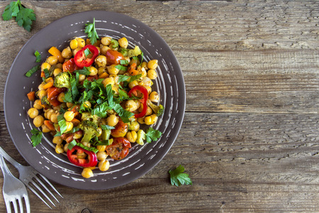 Homemade spicy vegetarian stew with chickpeas and vegetables over rustic wooden background with copy space - healthy vegetarian food
