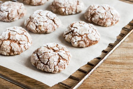 Chocolate crinkle cookies on baking paper with copy space - homemade winter chocolate christmas pastry