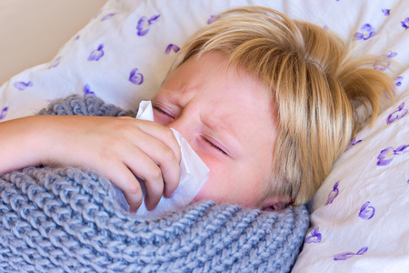 Sick little child boy blowing nose laying in bed with sad face - healthcare and medicine concept