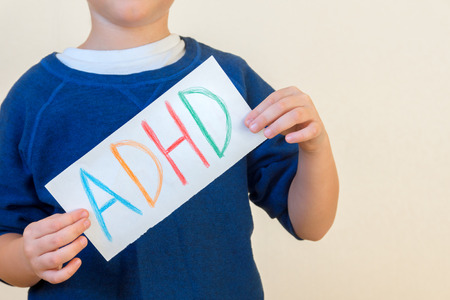 hyperactivity: Young boy holds ADHD text written on sheet of paper. ADHD is Attention deficit hyperactivity disorder.
