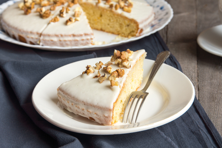 walnut cake: Homemade pumpkin and walnut cake with sour cream icing over rustic wooden table - healthy homemade pastry
