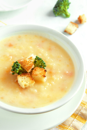 stilton: Vegetable and cheddar cheese cream soup with broccoli and croutons in white bowl close up - homemade heathy vegetarian food Stock Photo