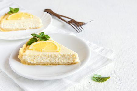 Pieces of delicious homemade lemon cheesecake with slices of lemon and mint on white background with copy space 版權商用圖片 - 65860307