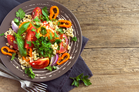 Fresh organic tomato and couscous salad with vegetables and greens - healthy vegetarian salad over rustic wooden table with copy space
