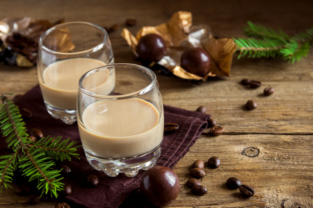 Irish cream coffee liqueur with chocolate candies, Christmas decoration and ornaments over rustic wooden background - homemade festive Christmas alcoholic drink Stockfoto