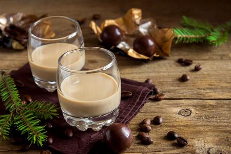 Ierse Room Coffee Likeur Met Chocolade Snoepjes, Kerstversiering en Ornamenten Over Rustieke Houten Achtergrond - Zelfgemaakte Feestelijke Kerstmis Alcoholische Drank