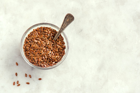 linum: Flax seeds in bowl on stone background with copy space - organic ingredient for healthy vegetarian vegan nutrition