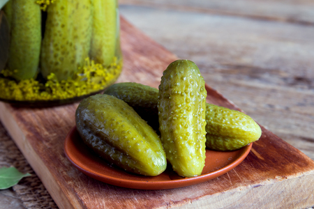 marinated gherkins: Pickles. Pickled gherkins (cucumbers) on ceramic plate over rustic wooden background with copy space. Stock Photo