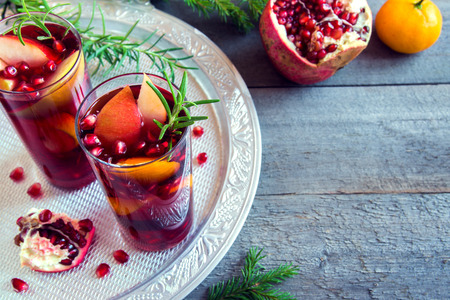 Christmas, autumn or winter sangria with oranges, apples, pomegranate seeds, rosemary and spices - homemade festive drink for Christmas time