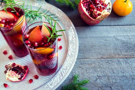 Sangria kerst, herfst of winter met sinaasappels, appels, granaatappelpitten, rozemarijn en specerijen - zelfgemaakte feestelijk drankje voor de kerst