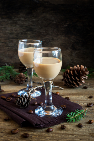 Irish cream coffee liqueur with coffee beans, Christmas decoration and cones over rustic wooden background - homemade festive Christmas alcoholic drink Фото со стока