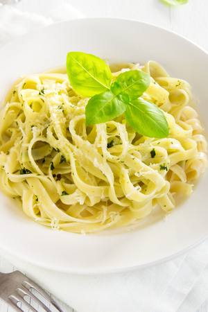 Tagliatelle pasta with pesto sauce, cheese and basil leaves on white plate close up - healthy homemade pasta
