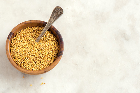 indian mustard: Mustard seeds in wooden bowl over white stone background with copy space - healthy food ingredient Stock Photo