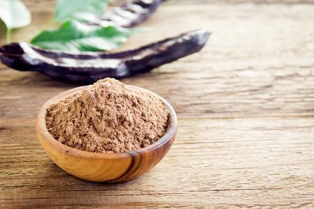 Johannesbroodpeulen en johannesbroodpoeder over houten achtergrond met exemplaarruimte - organisch gezond ingrediënt voor veganist vegetarische voedsel en dranken