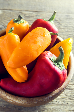 Fresh sweet organic bell peppers on  wooden background with copy space - healthy raw food ingredient