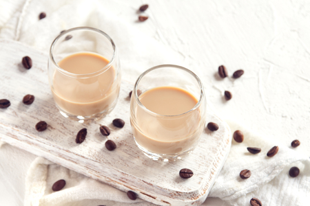 Irish cream coffee liqueur and coffee beans over white wooden background - homemade festive alcoholic drink Stock Photo