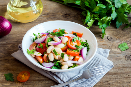 Fresh Cannellini Bean Salad with Cherry Tomatoes, Onion and Parsley on wooden background, copy space - healthy homemade organic vegetarian vegan diet protein salad meal food lunch