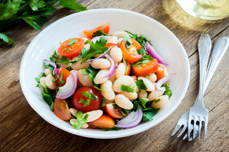 leguminosas: Fresh Cannellini Bean Salad with Cherry Tomatoes, Onion and Parsley on wooden background, copy space - healthy homemade organic vegetarian vegan diet protein salad meal food lunch