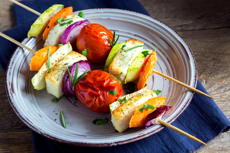 Halloumi cheese and vegetables grilled skewers on plate with spices and herbs close up - healthy vegetarian vegan diet barbecue grilled vegetable homemade meal Stock Photo